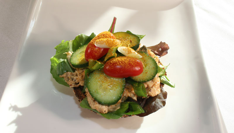 Tuna Salad Toasted Bagel Sandwich with Cucumber, Tomato, Green Onion and Sprinkled with Sweet Curry