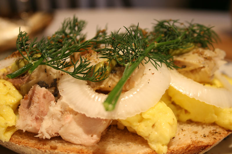 smoked mackerel with roasted garlic, scrambled eggs, dukkah, dill, onions and tarragon mustard sandwich.