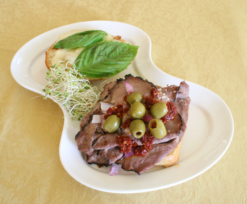 Spicy toasted roast beef cheese sandwich with sprouts and fresh basil