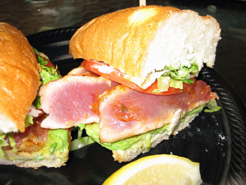 Seared Ahi Tuna Sandwich with Chipotle Seasoning served on soft boleo roll with lettuce, tomato, red onion and tartar.