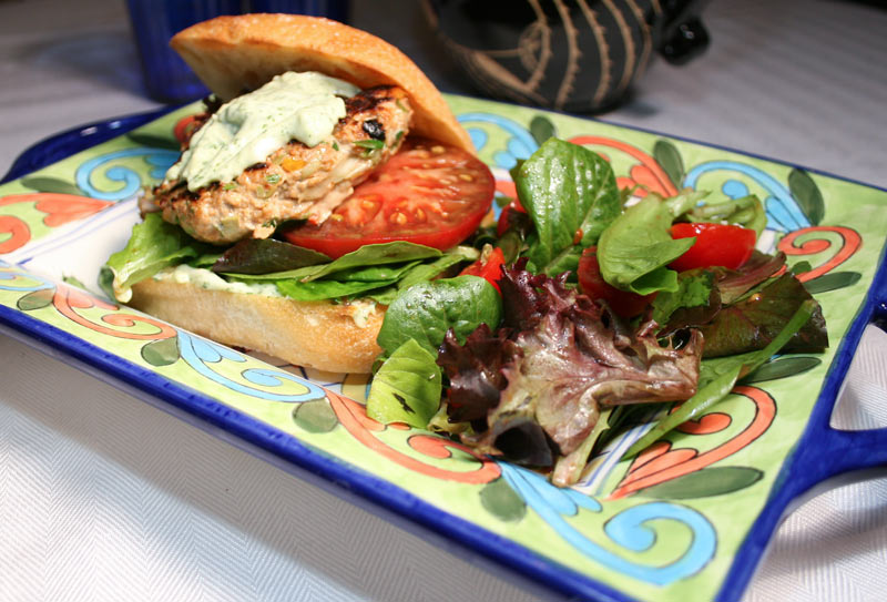 Salmon Burger on Ciabatta with cilantro Dressing, Lettuce and Tomato