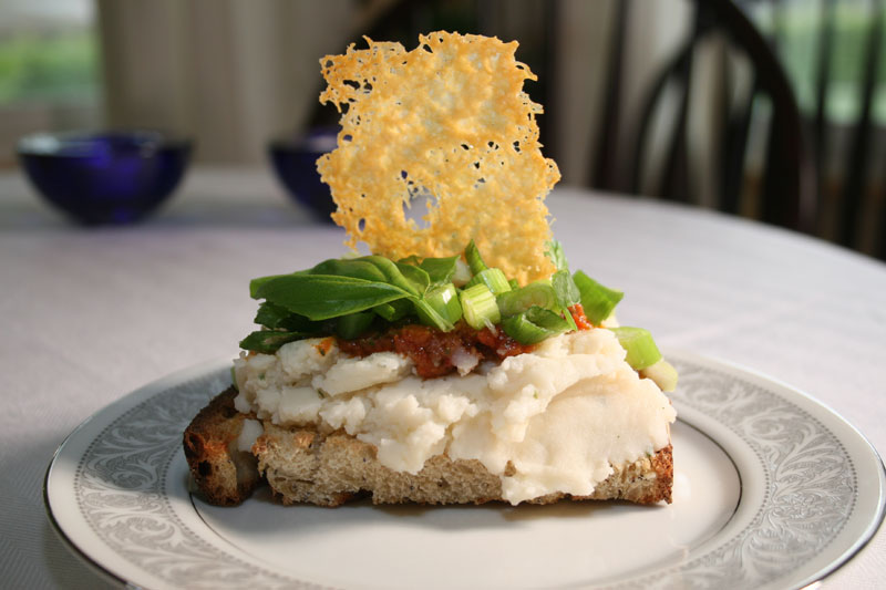 Mashed Potato Sandwich with Sun Dried Tomato Pesto, Green Onions, Sweet Basil Leaves, and Parmesan Crisp