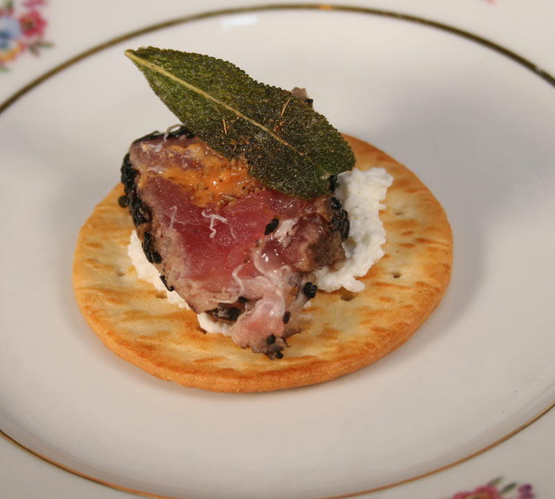 Seared tuna appetizer on cracker with ricotta cheese, vodka mustard smear and cumin salt with sage fried leaf