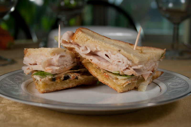 Turkey Sandwich with Lettuce, Fennel Seeds, Muffaletta, White Bean Tuscan Paste, Paprika, Fresh Sweet Basil Leaves and Creamy Cheese