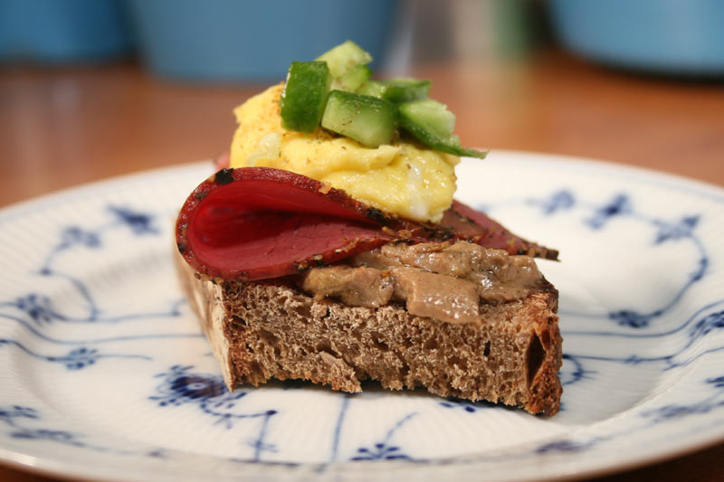 Chicken Truffle Mousse Pate Sandwich With Pastrami, Scrambled Eggs, Dukkah And Cucumber on Lingonberry Bread