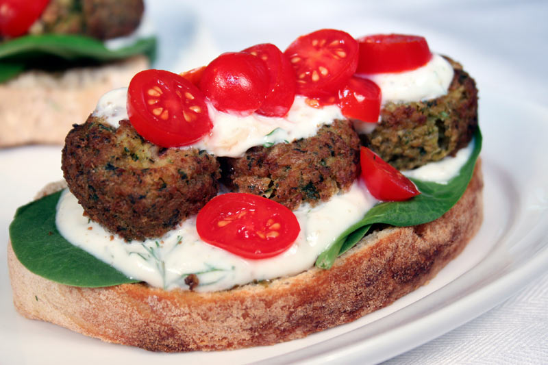 Falaffel Sandwich with Garlic-Yogurt Dressing, Lime, Pesto, Spinach and Grape Tomatoes on Ciabatta Bread
