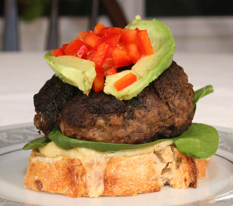Feta-Stuffed Burger With Avocado, Red Bell Peppers On Spinach And Dubliner Cheese