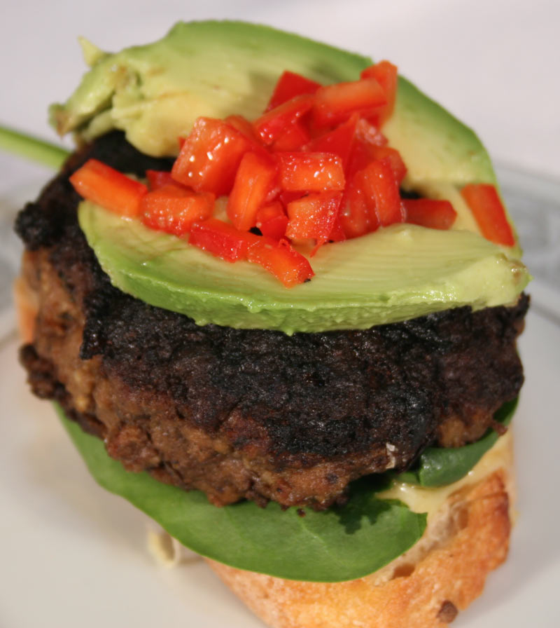 Feta-Stuffed Burger With Avocado, Red Bell Peppers On Spinach And ...
