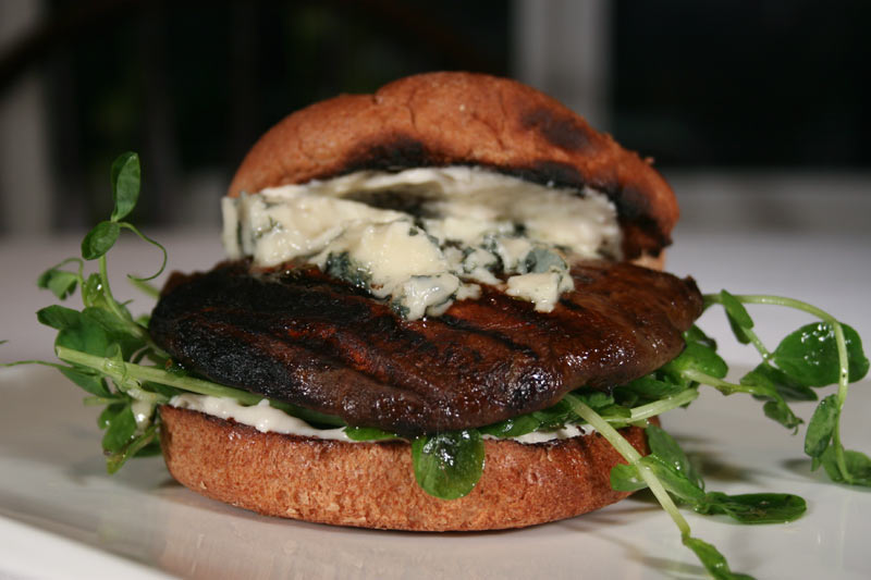 Portobello Mushroom Burger With Roquefort On Bed Of Pea Sprouts