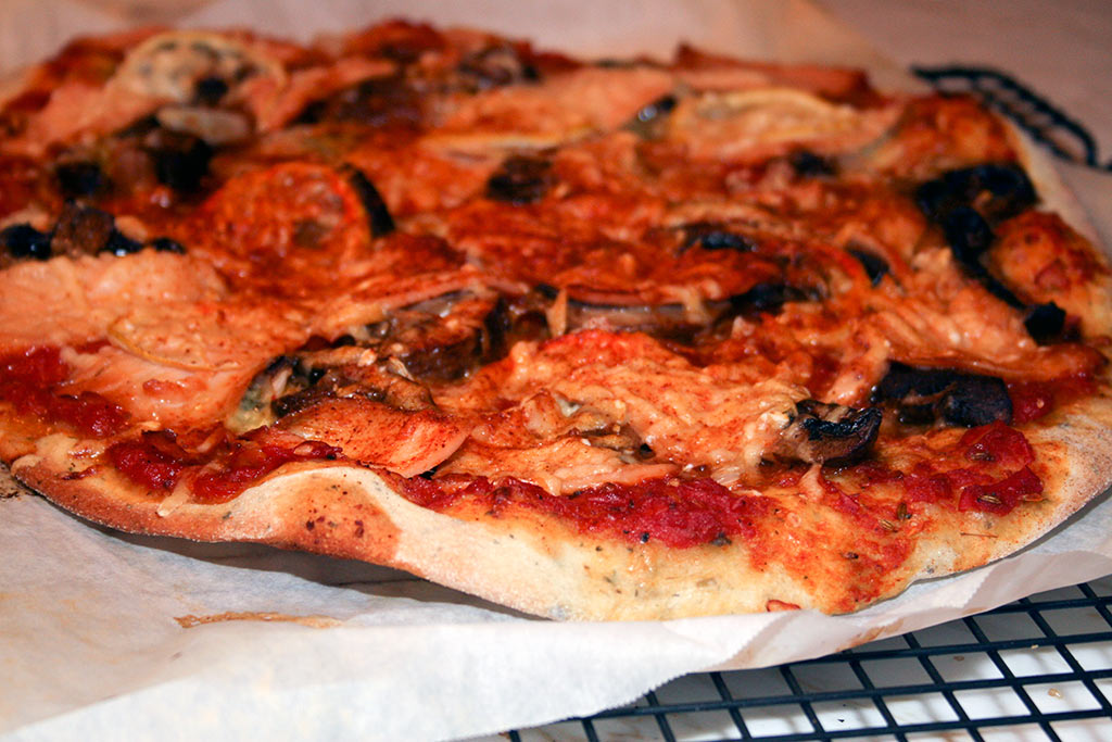 Smoked Salmon Pizza With Butter Garlic Fried Portobello Mushrooms And Parmesan Wafer thin slices of Lemon, Onion, Stilton Blue Cheese, Smoked Paprika, Tomato Sauce with Honey and Anise