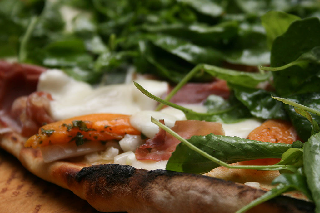 Apricot prosciutto pizza with mozzarella and arugula